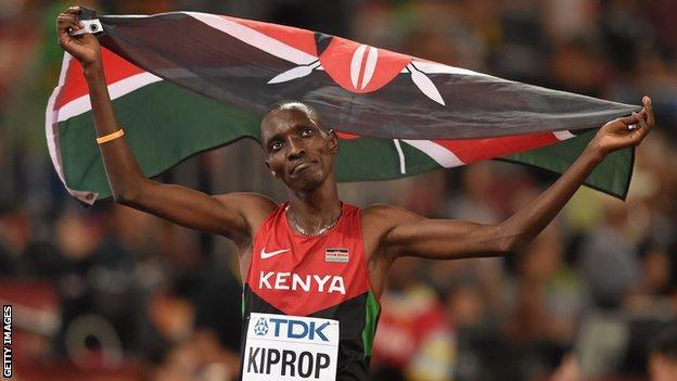 Kenya's Asbel Kiprop celebrates by raising the Kenyan flag after winning gold in the men's 1500m final at the 2015 World Championships
