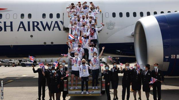 Team GB athletes pose with medals getting off a plane