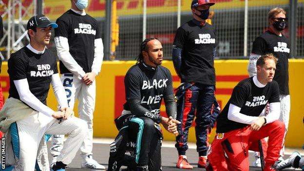 Lewis Hamilton and fellow F1 drivers take part in an anti-racism protest before Sunday's British Grand Prix