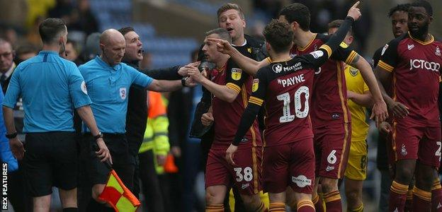 Oxford United's manager Karl Robinson protects referee Andy Davies as controversy breaks out over the winning goal against Bradford