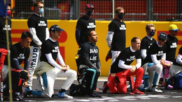 Charles Leclerc (far left) was one of seven drivers to remaining standing during the British Grand Prix as other drivers 'took a knee'