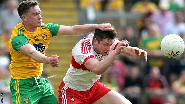 Donegal's Ciaran Thompson puts in a strong challenge on Derry forward Emmet Bradley
