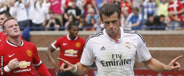 Gareth Bale celebrates scoring for Real Madrid against Manchester United as Wayne Rooney looks on