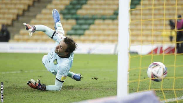 Norwich keeper Tim Krul tries to stop Lloyd Kelly's shot