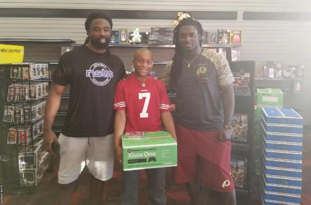Jaden Watts receives his Xbox from two NFL players