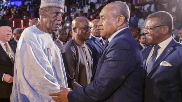 Issa Hayatou (with hat) shakes hands with Ahmad
