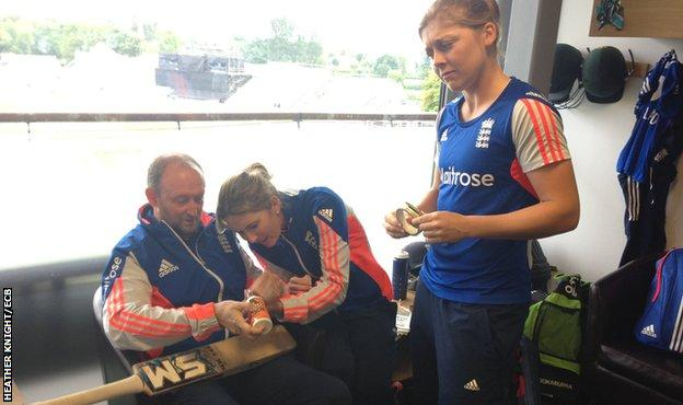 Heather Knight watches captain Charlotte Edwards repair her bat