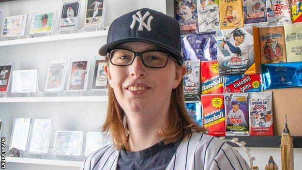 Laura Brain in front of her sports cards and memorabilia collection