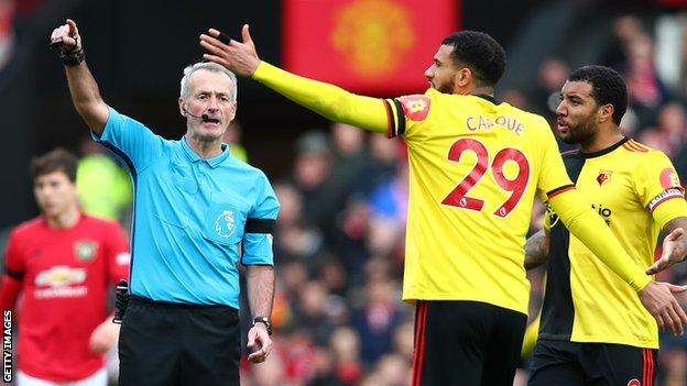 Troy Deeney and Etienne Capoue speak to referee Martin Atkinson