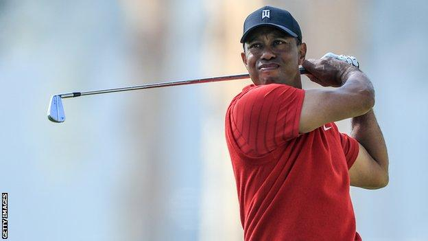 Tiger Woods looks on after playing a shot