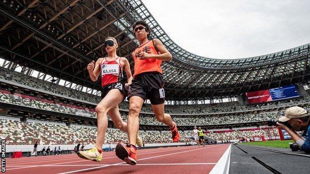 Japan's Hiroaki Kajisa and his guide runner
