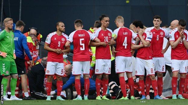Denmark players form a ring around Christian Eriksen
