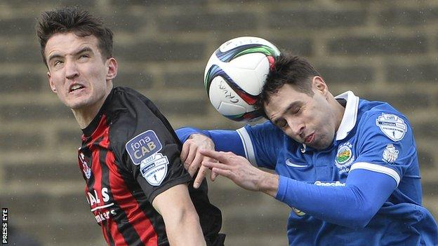 Josh Robinson battles with Linfield's Sean Ward during the Premiership game in April