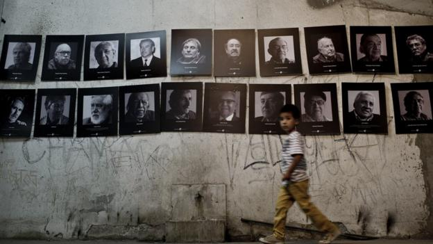Boy walks past photos of political prisoners at the Santiago Stadium in Chile