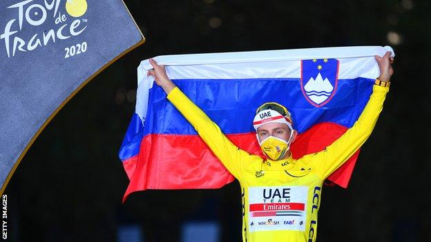 Tadej Pogacar holds up the Slovenian flag in celebration after winning the 2020 Tour de France