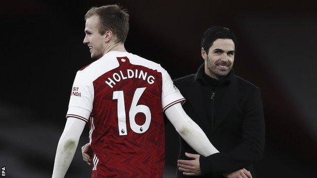 Rob Holding and Mikel Arteta embrace after Arsenal's win against Chelsea