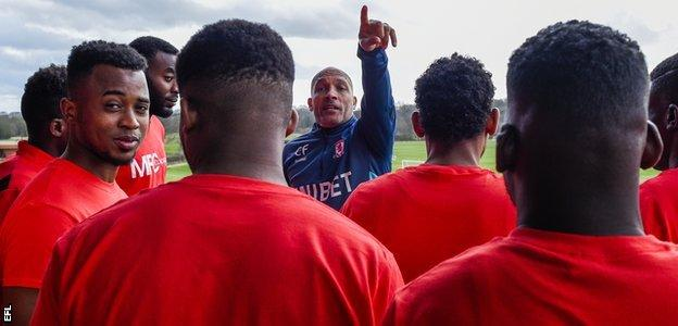 Middlesbrough coach Curtis Fleming shows refugee footballers around the club's training base
