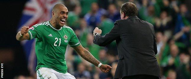 Josh Magennis celebrates with manager Michael O'Neill after scoring his side's second goal in the 3-1 win against Greece