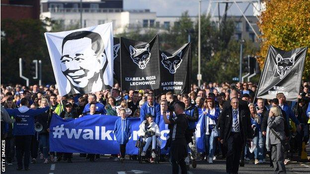 Fans hold up banners during the 'Walk for Vichai'