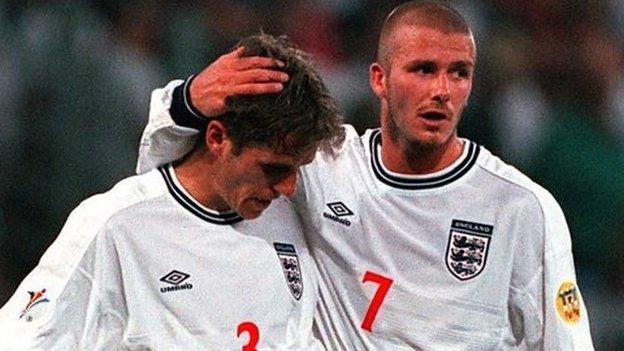 Phil Neville is consoled by David Beckham