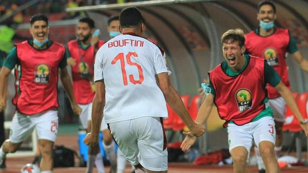 Soufiane Boutfini celebrates with team-mates after setting Morocco on their way to a second successive CHAN final