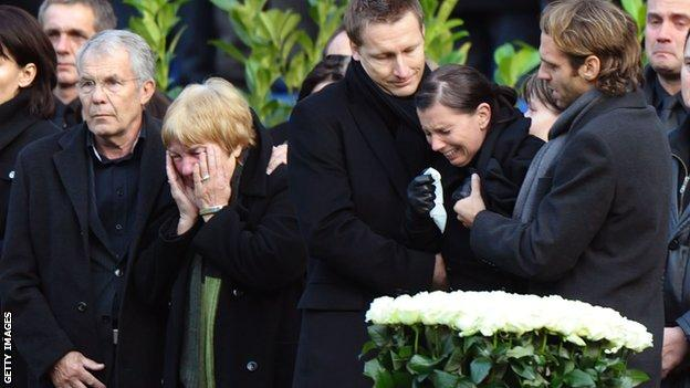 Teresa is supported by Enke's friend and agent Jörg Neblung at her husband's funeral