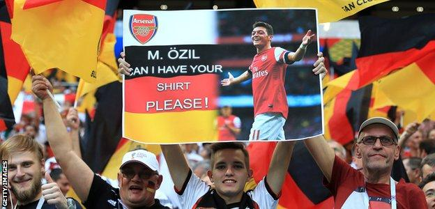 German fans hold up a sign asking for Mesut Ozil's shirt