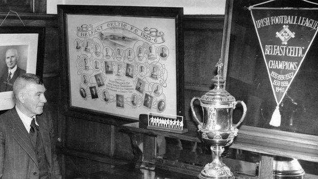 Belfast Celtic manager Elisha Scott looks proudly at the silverware in the club boardroom