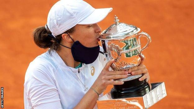 Iga Swiatek kisses the French Open trophy