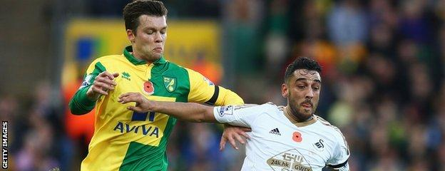 Jonny Howson vies with Neil Taylor