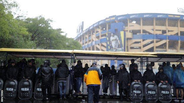 Riot police shelter from the rain outside Boca's La Bombonera stadium