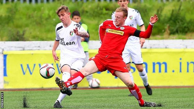 Glentoran's Jonathan Smith is tackled by Cliftonville captain George McMullan