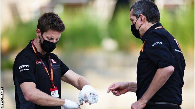 Roman Grosjean with bandaged hands talking to Haas F1 Team Principal Guenther Steiner