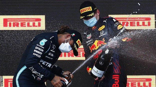 Max Verstappen and Lewis Hamilton spray champagne on the podium