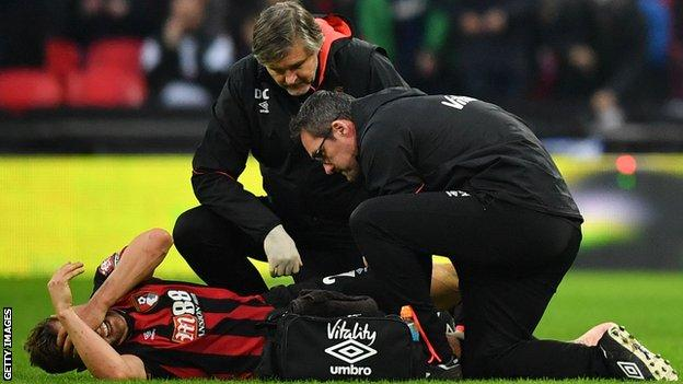 Bournemouth captain Simon Francis puts his hands over his head in agony as he receives medical treatment for a knee injury on the pitch against Tottenham