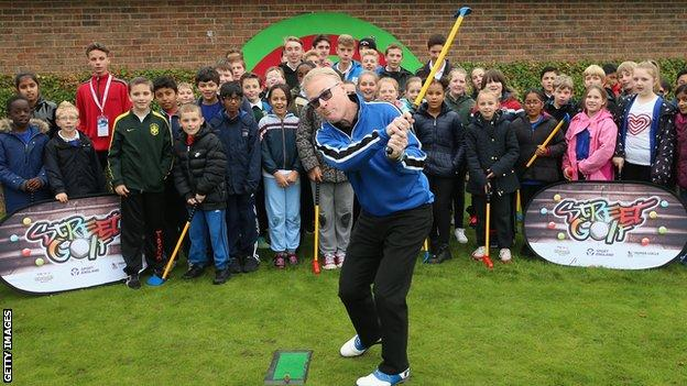 Keith Pelley, Chief Executive of The European Tour, plays a shot as he watched by members of the Golf Foundation's Street Golf