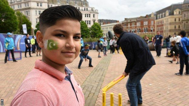 A South Asian boy joining in a game of street cricket