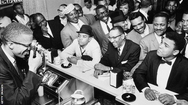 Malcolm X takes a picture of Muhammad Ali in the Hampton House cafe the night the boxer won his first fight with Sonny Liston