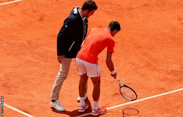 Novak Djokovic challenges a line call with the umpire