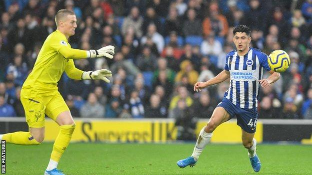 Steven Alzate challenges for a ball with Jordan Pickford
