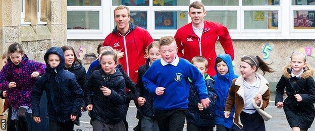Robbie Renwick and Ross Murdoch with school children in Stirling