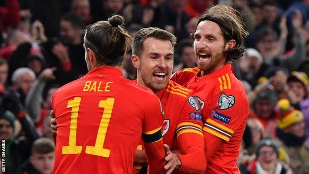Joe Allen (R) celebrates Euro 2020 qualification with Wales team-mates Aaron Ramsey and Gareth Bale