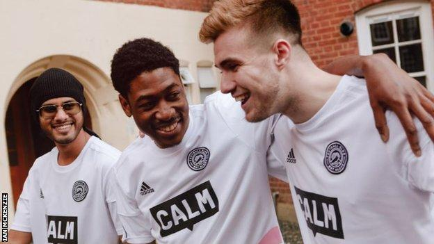 Members of the FC Not Alone squad share a joke wearing their kit