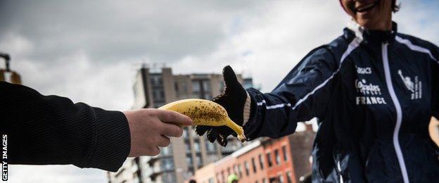 A volunteer giving a banana to a runner