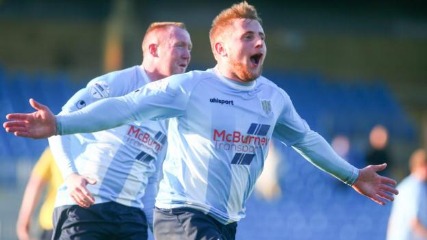 David Cushley runs to celebrate with Ballymena supporters after scoring his side's winner against Dungannon in the final minute