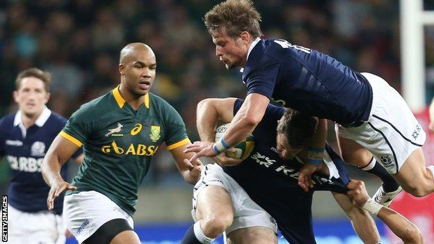 Cornal Hendricks of South Africa tackles Scotland's Tommy Seymour as Peter Horne falls over the top of them during the Test at Nelson Mandela Bay Stadium in 2014