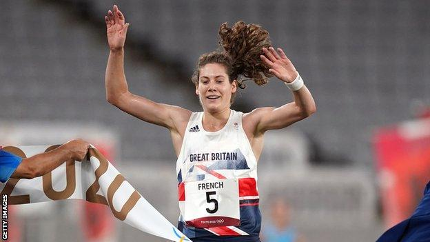 Kate French crosses the line with arms aloft