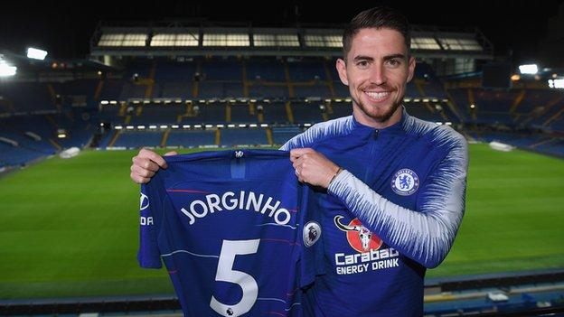 Jorginho holding a Chelsea shirt after signing for the Premier League club from Napoli