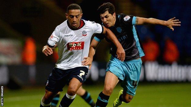 Liam Feeney of Bolton is tackled by Fernando Forestieri of Sheffield Wednesday