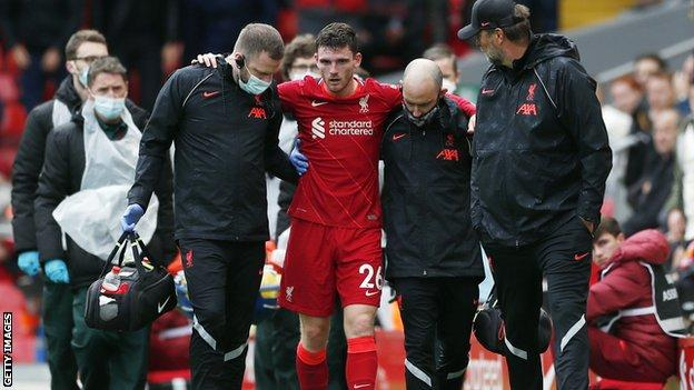 Andy Robertson helped off the pitch in pain